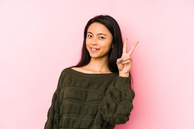 Giovane donna cinese su una parete rosa allegra e spensierata mostrando un simbolo di pace con le dita.