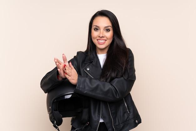 Giovane donna colombiana che tiene un casco del motociclo sopra l'applauso isolato della parete