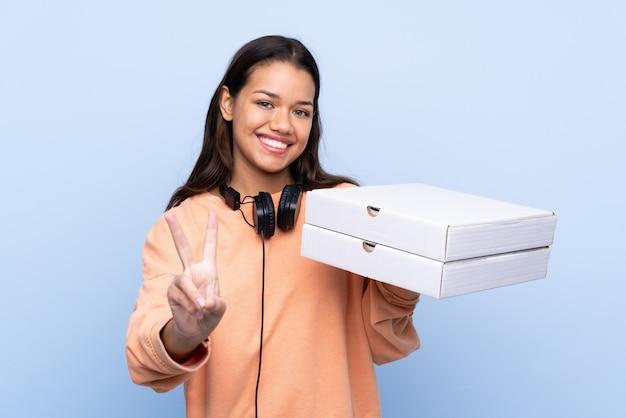 Giovane donna colombiana che tiene una pizza sopra la parete blu isolata che sorride e che mostra il segno di vittoria