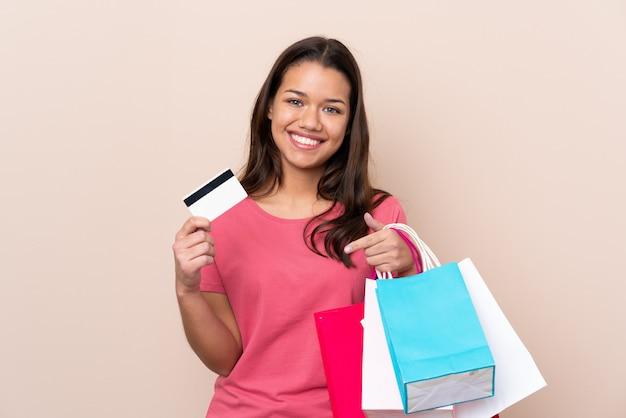 Giovane donna colombiana con il sacchetto della spesa sopra i sacchetti della spesa isolati della tenuta della parete e una carta di credito