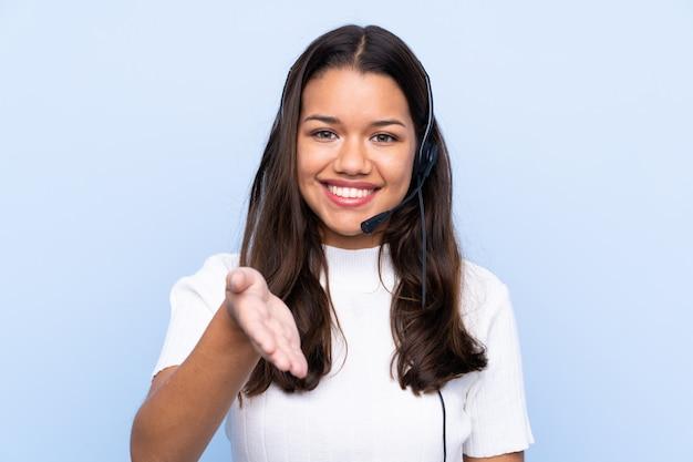 Giovane donna colombiana di telemarketer sopra la stretta di mano isolata della parete blu dopo il buon affare