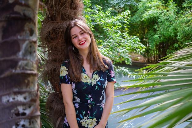 Giovane donna con abiti eleganti in posa in un parco paradisiaco al tramonto