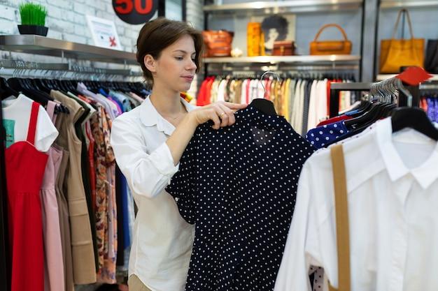 Giovane donna con abito nero nelle sue mani in boutique