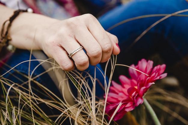 Giovane donna con anello in mano che riposa sull'erba vicino a un fiore rosa.