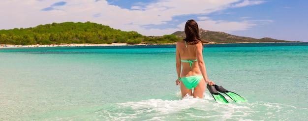 Giovane donna con attrezzatura per lo snorkeling sulla spiaggia tropicale
