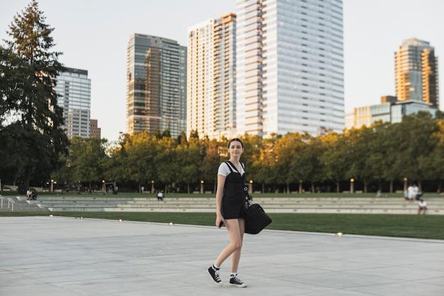 Giovane donna con bagaglio sul parco urbano