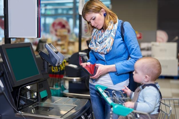 Giovane donna con bambino pagando con self checkout