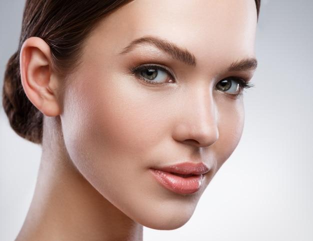 Giovane donna con bel viso e pelle morbida