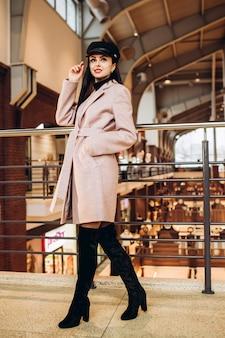 Giovane donna con berretto in pelle nera, cappotto e stivali lunghi