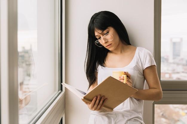 Giovane donna con bevanda leggendo vicino a windows