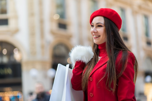 Giovane donna con borse della spesa a milano, italia