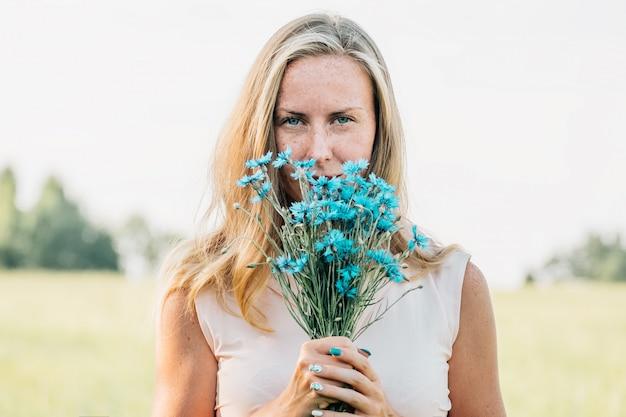 Giovane donna con bouquet di fiordalisi