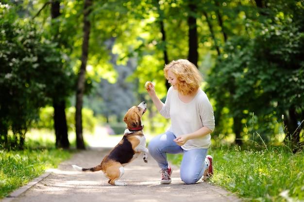Giovane donna con cane beagle nel parco estivo. animale domestico ubbidiente con il suo proprietario che pratica il comando di salto