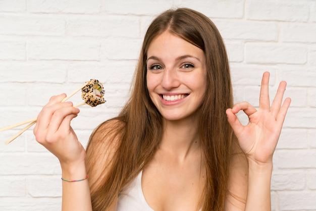 Giovane donna con capelli lunghi che mangia annd dei sushi che fanno segno giusto