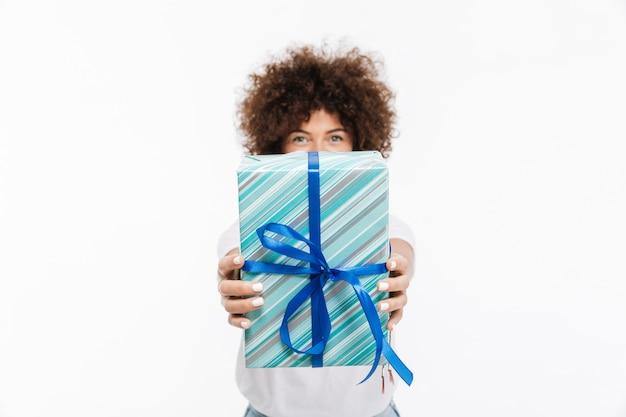 Giovane donna con capelli ricci che mostra il contenitore di regalo