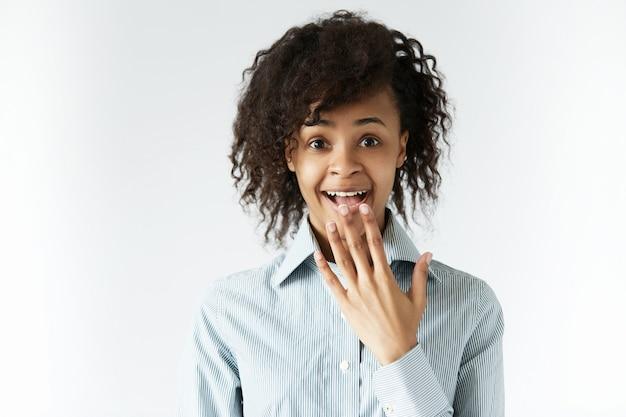 Giovane donna con capelli ricci e camicia a righe