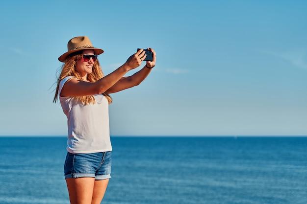 Giovane donna con cappello a fotografare il mare al largo della costa in estate