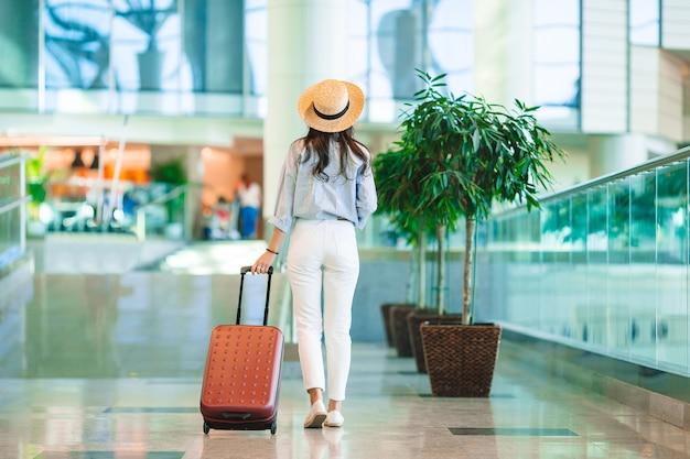 Giovane donna con cappello con bagaglio in aeroporto internazionale.