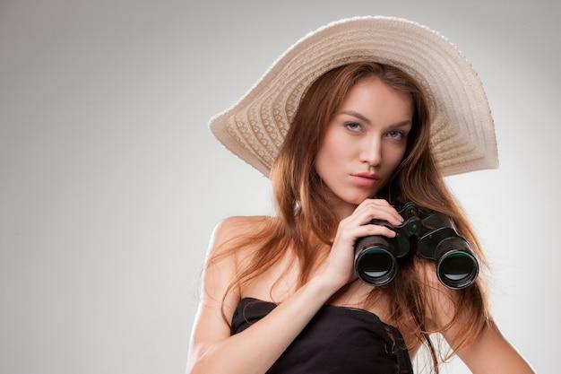 Giovane donna con cappello con binocolo