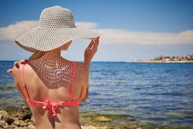 Giovane donna con cappello con crema solare a forma di sole sulla schiena.