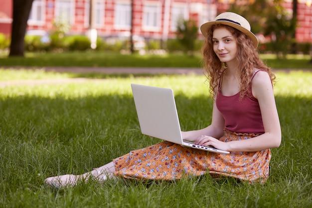 Giovane donna con cappello di paglia, maglietta bordeaux e gonna seduta sull'erba verde e navigare in internet con il suo portatile bianco, ha lezioni online, attraente donna con capelli ondulati e voluminosi studia aria aperta.