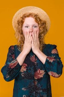 Giovane donna con cappello e chiedendo capelli ricci