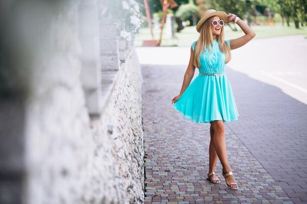 Giovane donna con cappello e vestito blu fuori nel parco