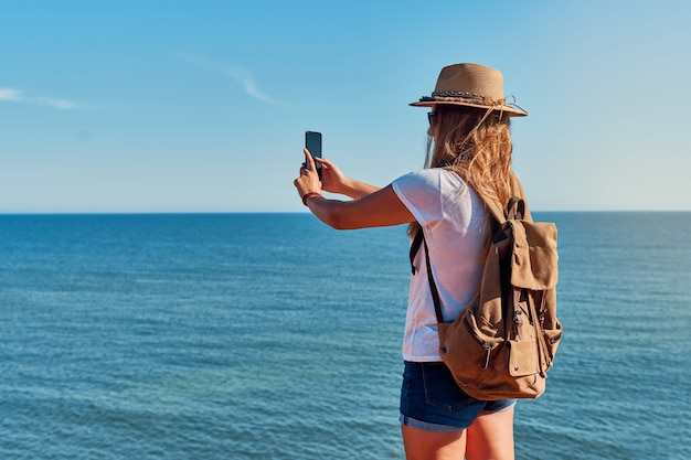 Giovane donna con cappello e zaino, fotografando il mare al largo della costa in estate
