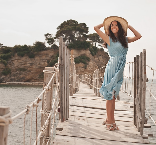 Giovane donna con cappello estivo in posa sul ponte
