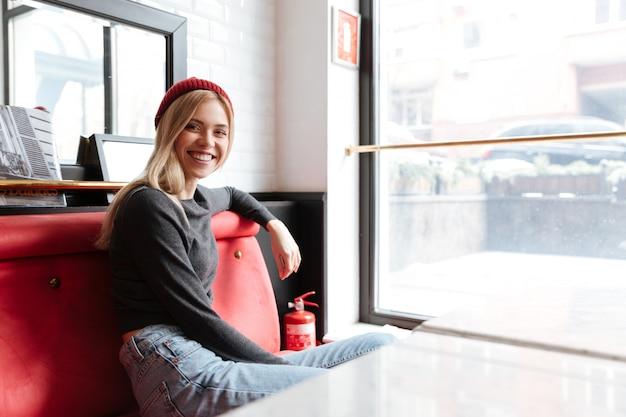Giovane donna con cappello rosso seduto al tavolo