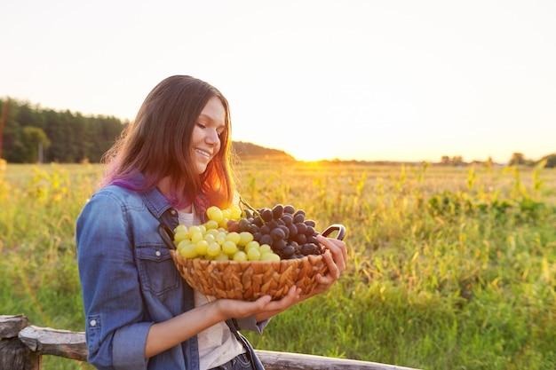 Giovane donna con cesto di uva blu e verde