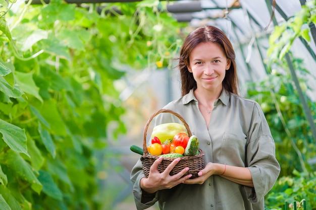 Giovane donna con cesto di verde e verdure in serra. tempo di raccolta