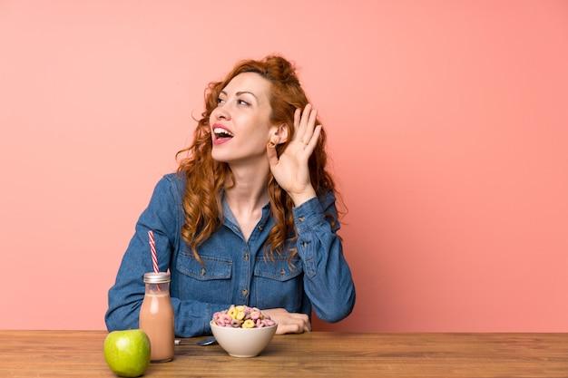Giovane donna con colazione oltre rosa isolato