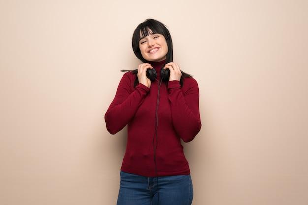 Giovane donna con collo alto rosso con le cuffie