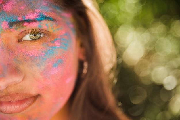 Giovane donna con colore holi rosa e blu sul suo viso