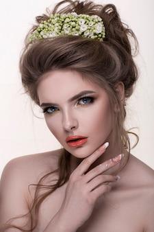 Giovane donna con corona di fiori. trucco professionale