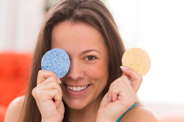 Giovane donna con cuscini cosmetici