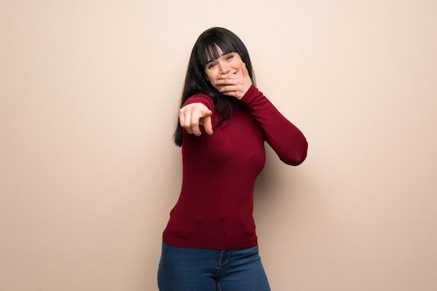 Giovane donna con dolcevita rosso che puntava il dito contro qualcuno e ridendo