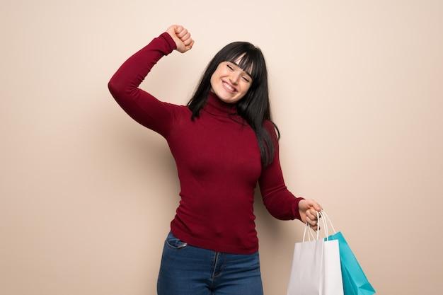Giovane donna con dolcevita rosso che tiene molti sacchetti della spesa nella posizione di vittoria