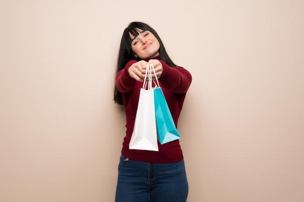 Giovane donna con dolcevita rosso che tiene molti sacchetti della spesa
