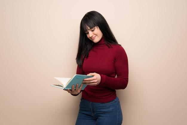 Giovane donna con dolcevita rosso che tiene un libro e che gode della lettura