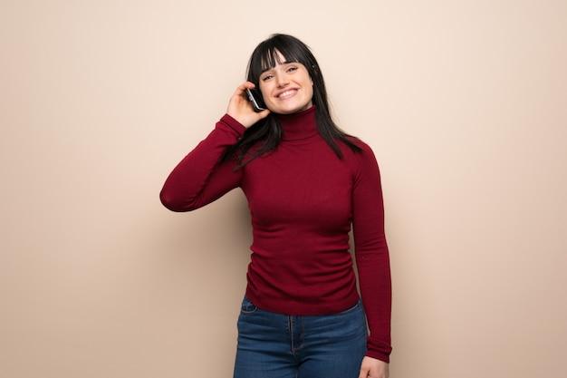 Giovane donna con dolcevita rosso mantenendo una conversazione con il telefono cellulare