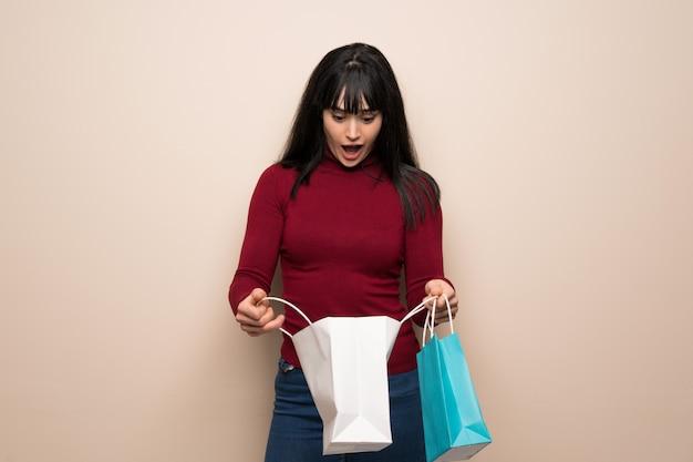Giovane donna con dolcevita rosso sorpreso mentre si tiene un sacco di borse per la spesa