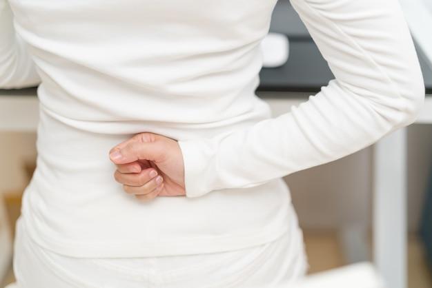 Giovane donna con dolore alla schiena che lavora con l'assistenza sanitaria del computer e il concetto medico