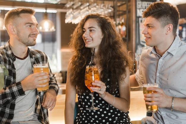 Giovane donna con due amici maschi tenendo bicchieri di bevande