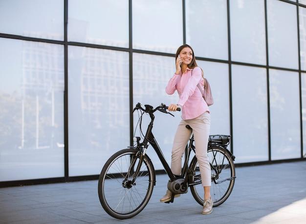 Giovane donna con ebicycle utilizzando sul telefono cellulare