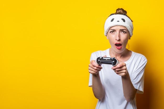 Giovane donna con espressione focalizzata con un joystick in mano, gioca un gioco virtuale.