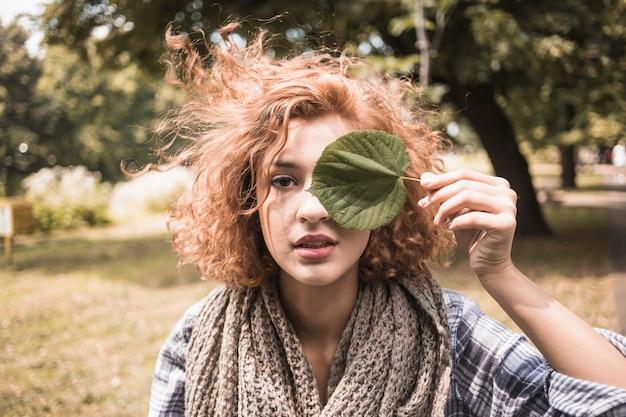 Giovane donna con foglia nel parco