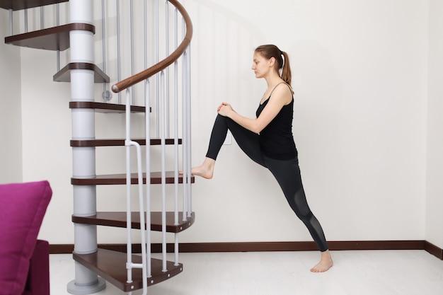 Giovane donna con forma del corpo sottile in abiti sportivi facendo esercizio