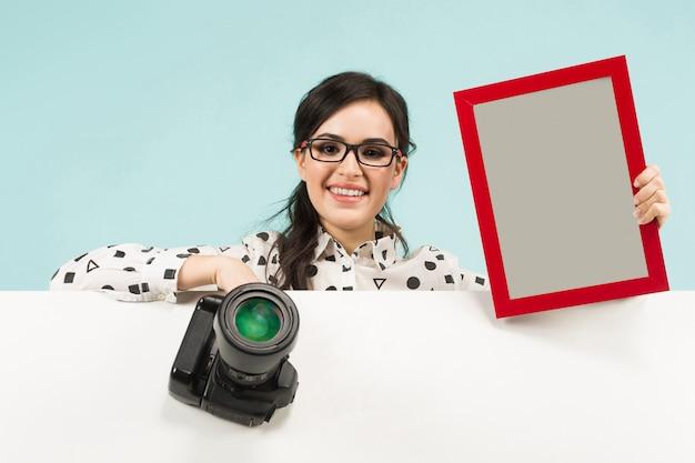 Giovane donna con fotocamera e telaio
